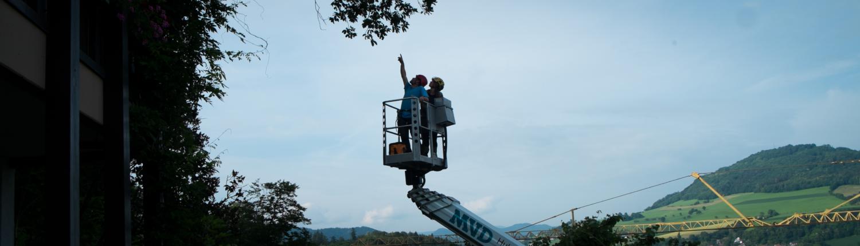 Zwei Mitarbeiter auf einem Hubsteiger in der Höhe.